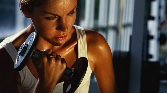 Model Released: Woman exercising with weights in gym, close-up (Photo by Zoran Milich/Getty Images)